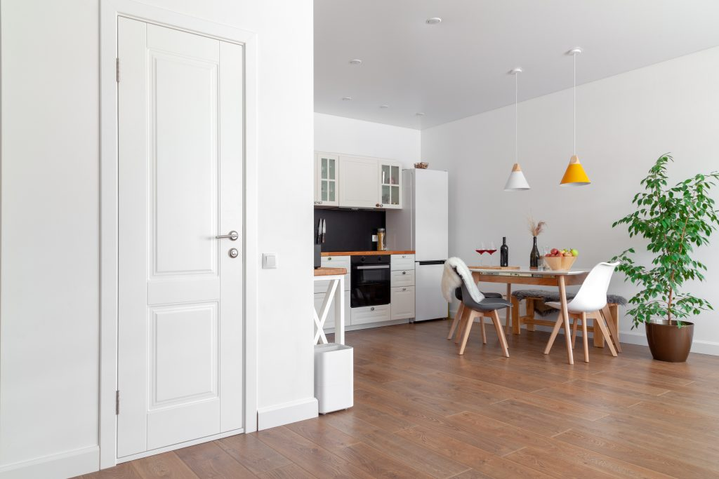 Modern interior of cozy kitchen, dining room, white furniture, wall, black accessories, natural materials, wooden chairs, green flower in pot. Concept scandinavian design apartment of young family