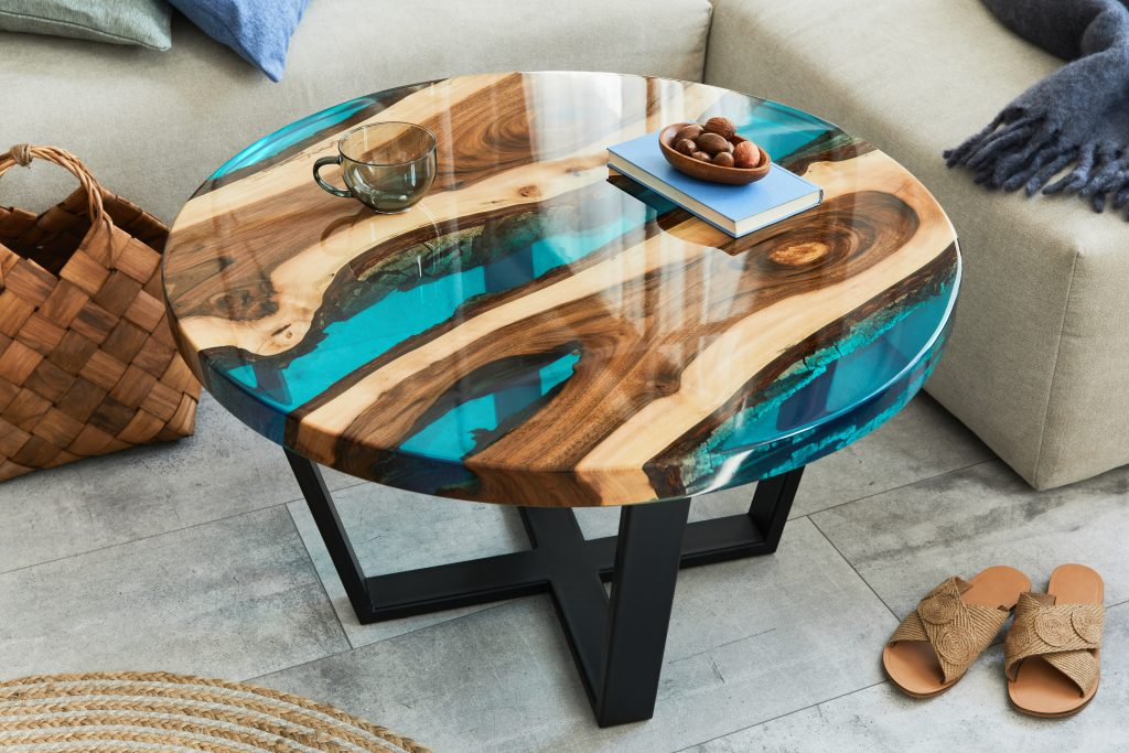 Stylish composition with design epoxy coffee table, sofa, blanke